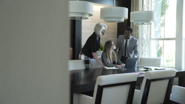 vídeos y material grabado en eventos de stock de handheld shot of business people discussing over laptop computer in meeting at board room - colega