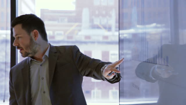 handheld shot of businessman explaining graph in meeting at board room - projektor stock-videos und b-roll-filmmaterial
