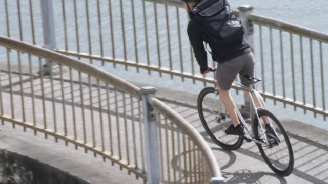 handheld shot of businessman riding bicycle on bridge in city - portland oregon bike stock videos & royalty-free footage