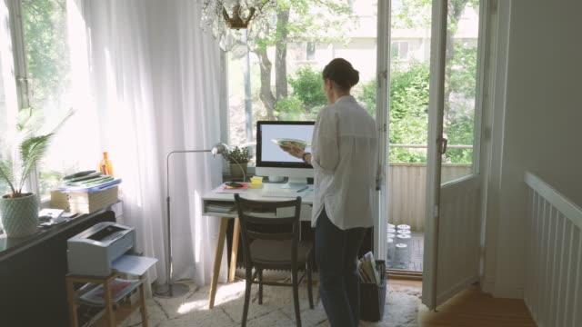 vidéos et rushes de handheld shot of businesswoman bringing food at computer desk in home office - bureau ameublement