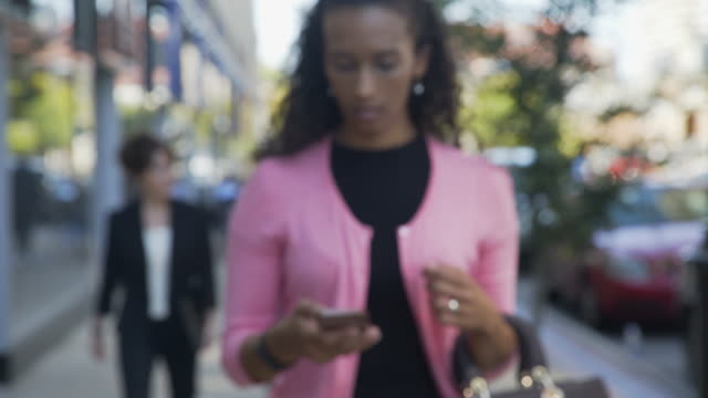 handheld shot of businesswoman using smart phone while colleagues walking in background - handbag stock videos & royalty-free footage