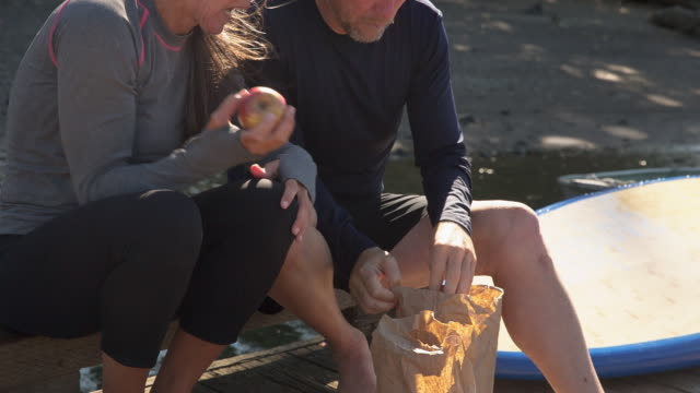 handheld shot of cheerful couple having food while sitting on pier - protein bar stock videos & royalty-free footage
