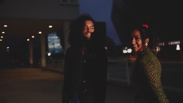 handheld shot of cheerful couple walking on footpath in city at night - nattliv bildbanksvideor och videomaterial från bakom kulisserna