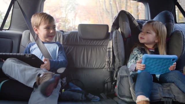 Handheld shot of children with tablet computers talking while traveling in car