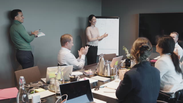 handheld shot of colleagues clapping and applauding while planning in board room during meeting - employee engagement stock videos & royalty-free footage