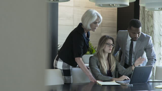 handheld shot of colleagues discussing over laptop computer in meeting at board room - colleague stock videos & royalty-free footage