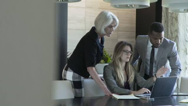 vídeos y material grabado en eventos de stock de handheld shot of colleagues discussing over laptop computer in meeting at board room - colega