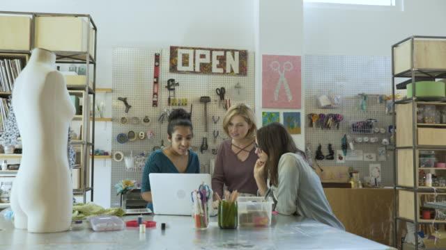 Handheld shot of confident businesswomen using laptop at desk in creative office