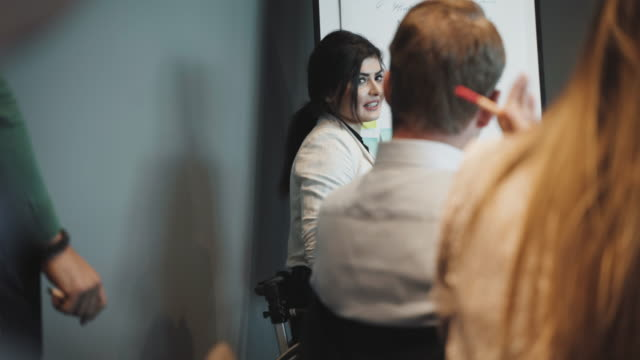 handheld shot of confident disabled businesswoman discussing with businessman in board room during meeting - employee engagement stock videos & royalty-free footage