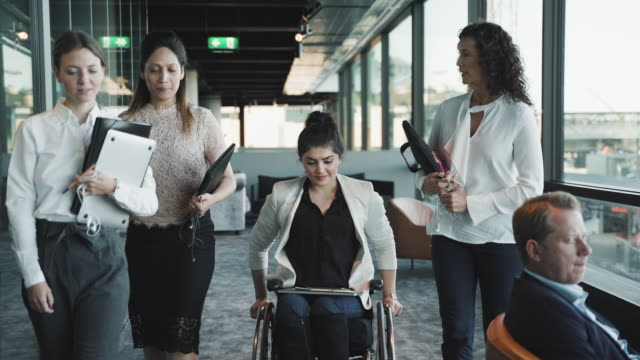 handheld shot of confident female colleagues discussing while moving in corridor at coworking office - employee engagement stock videos & royalty-free footage
