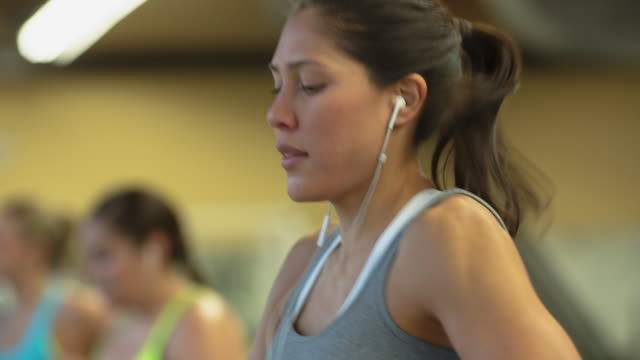 handheld shot of confident women running at gym - headshot stock videos & royalty-free footage