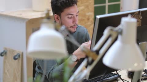 handheld shot of confident young businessman talking while using mobile phone at desk in office - skrivbord bildbanksvideor och videomaterial från bakom kulisserna