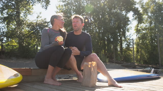 handheld shot of couple having food while sitting on pier - protein bar stock videos & royalty-free footage