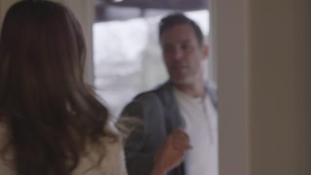 handheld shot of couple kissing while saying goodbye at doorway - saying goodbye stock videos & royalty-free footage