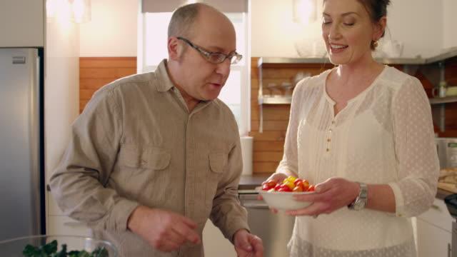 handheld shot of couple preparing food in kitchen - portland oregon homes stock videos & royalty-free footage
