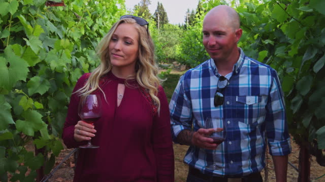 Handheld Shot of Couple Walking Through Vineyard with Glasses of Wine - Slow Motion