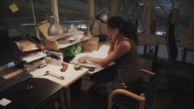 handheld shot of craftswoman analyzing documents while talking on the phone at workshop - skakig kamerabild bildbanksvideor och videomaterial från bakom kulisserna