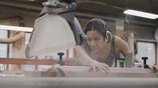 handheld shot of craftswoman cutting plank on table saw at illuminated workshop - shaky stock videos & royalty-free footage