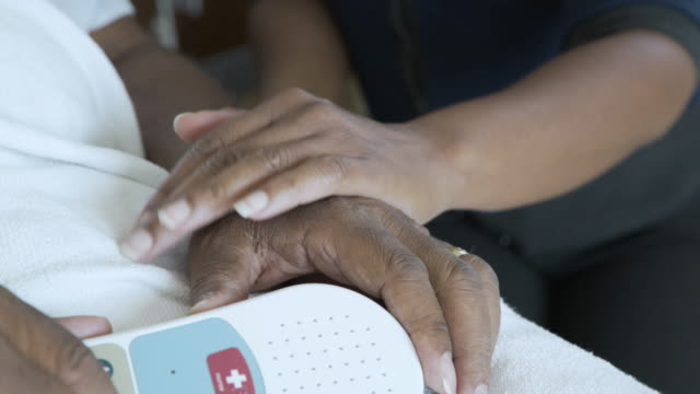 Handheld shot of daughter touching senior father's hand holding remote control at hospital ward