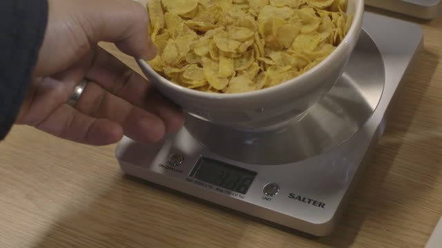 handheld shot of digital weighing scales being used to measure the amount of cereal in a bowl, uk. - scales stock videos & royalty-free footage