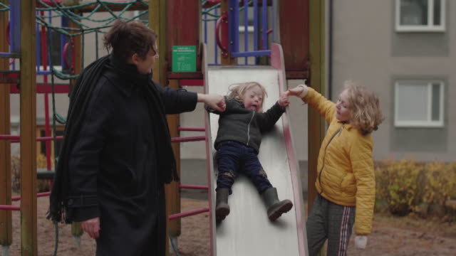handheld shot of disable girl with family playing on slide against building - sweden stock videos & royalty-free footage