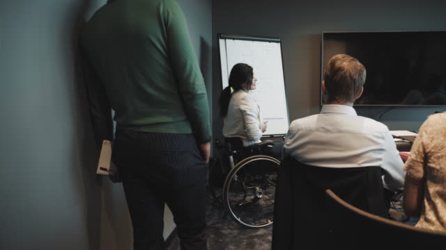 vídeos de stock e filmes b-roll de handheld shot of disabled female entrepreneur giving presentation to colleagues in board room at creative office - pessoas com deficiência