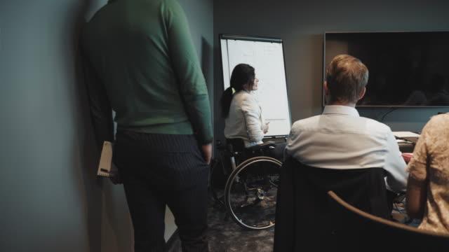 vídeos y material grabado en eventos de stock de handheld shot of disabled female entrepreneur giving presentation to colleagues in board room at creative office - personas con discapacidad