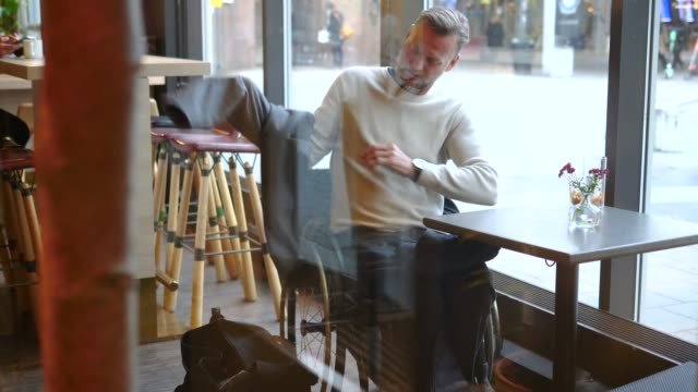 handheld shot of disabled mature businessman putting laptop in bag and wearing overcoat in restaurant - laptop bag stock videos and b-roll footage