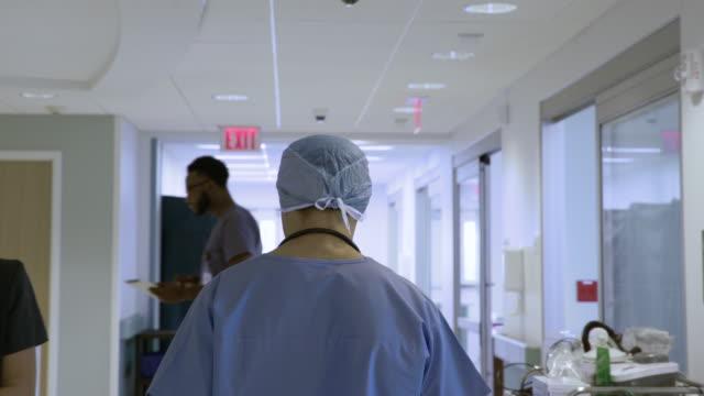 handheld shot of doctor wearing scrubs walking by colleagues in corridor at hospital - scrubs stock-videos und b-roll-filmmaterial