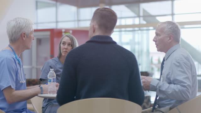 handheld shot of doctors discussing in meeting at hospital - ウォーターボトル点の映像素材/bロール