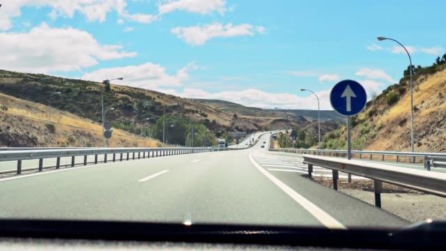 vídeos y material grabado en eventos de stock de disparo de mano de la vista de conducción desde el parabrisas del coche en una carretera - carretera