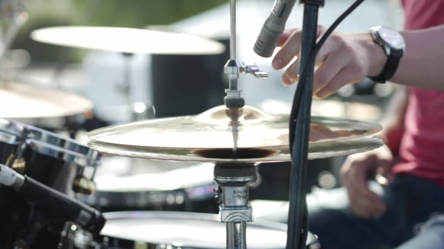 Handheld shot of drummer adjusting cymbals