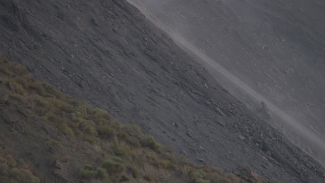 handheld shot of dust inching slowly over rock on the side of stromboli volcano, italy. - rock type stock videos and b-roll footage