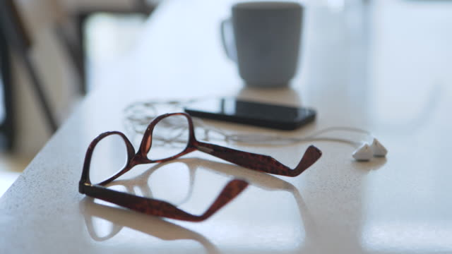 Handheld shot of eyeglasses with smart phone and headphones by coffee cup on table at home