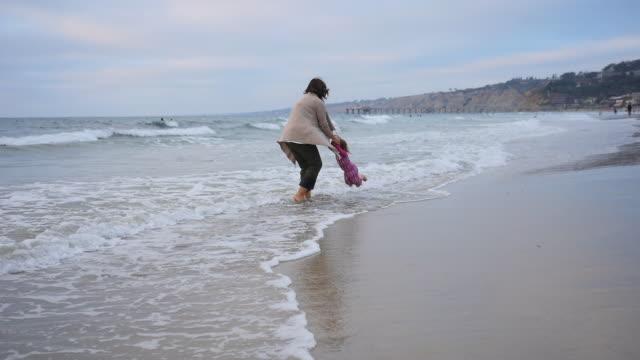 handheld shot of family enjoying at beach during sunset - mit handkamera stock-videos und b-roll-filmmaterial