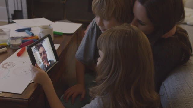 handheld shot of family on video conference with father at home - telecamera traballante video stock e b–roll