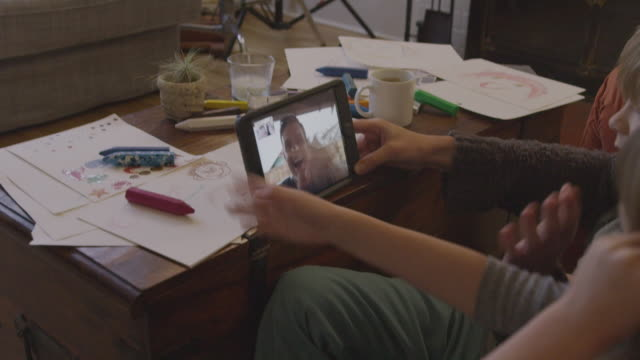 stockvideo's en b-roll-footage met handheld shot of family on video conference with father in living room at home - shaky