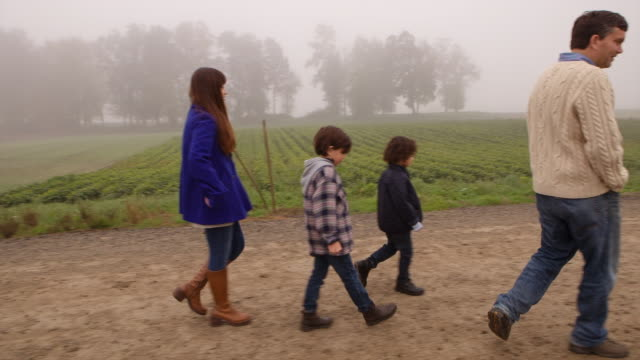 Handheld shot of family walking on dirt road in farm during foggy weather