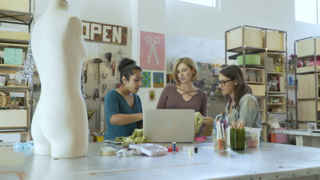 Handheld shot of fashion designers working in creative office