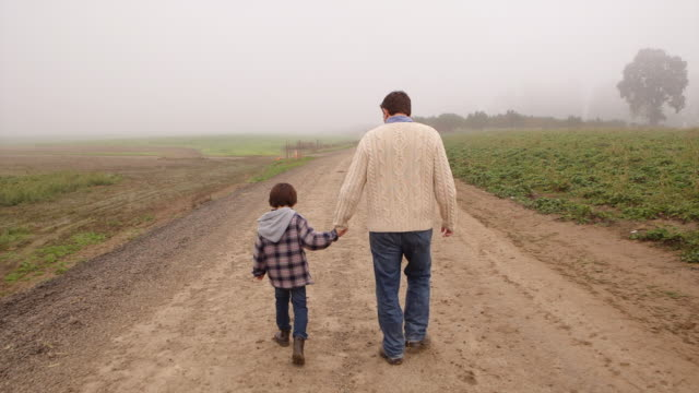 Handheld shot of father and son walking on dirt road in farm during foggy weather