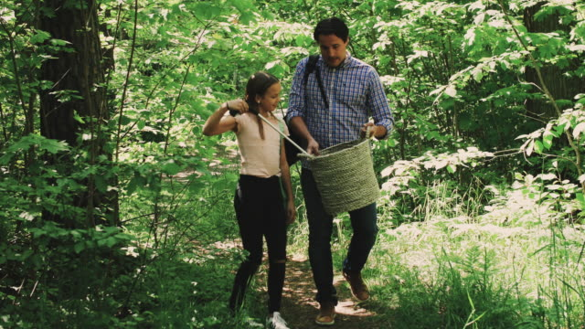 handheld shot of father pointing while daughter collecting garbage in forest - 北欧諸国点の映像素材/bロール