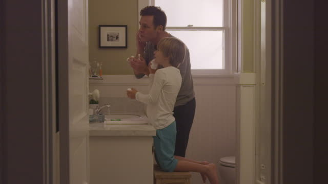 handheld shot of father with son applying shaving cream in bathroom seen through doorway - stool stock videos & royalty-free footage