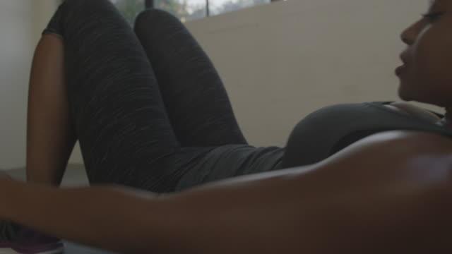 vídeos de stock, filmes e b-roll de handheld shot of female athlete exercising while lying on mat at gym - tatame tapetinho