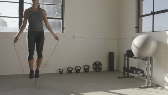handheld shot of female athlete exercising with jumping rope in gym - skipping stock videos & royalty-free footage