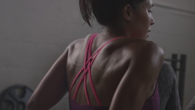 vidéos et rushes de handheld shot of female athletes exercising sit-ups in gym - quête de beauté