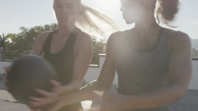 Handheld shot of female athletes exercising with medicine ball against sky on building terrace