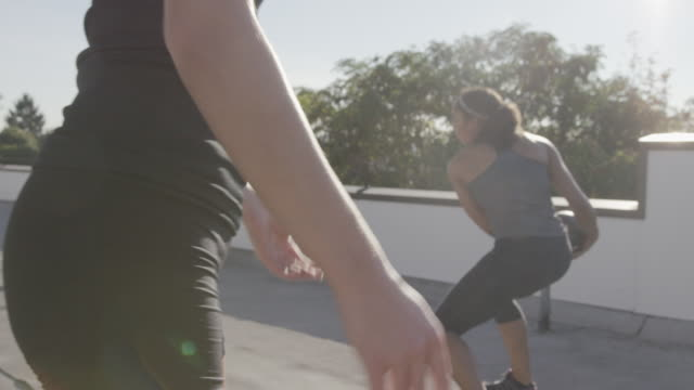 Handheld shot of female athletes exercising with medicine ball while standing on building terrace