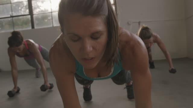 vidéos et rushes de handheld shot of female athletes practicing push-ups with dumbbells in gym - quête de beauté