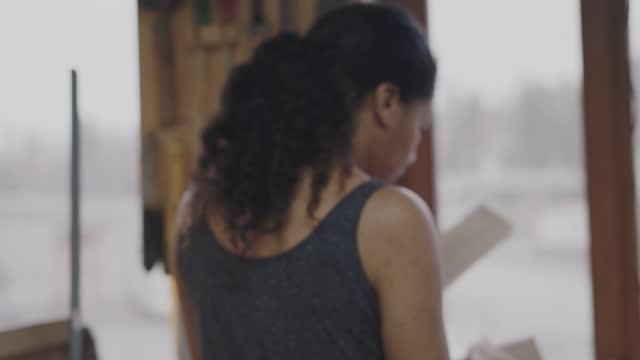 handheld shot of female carpenter carrying planks towards workbench and applying glue at workshop - skakig kamerabild bildbanksvideor och videomaterial från bakom kulisserna
