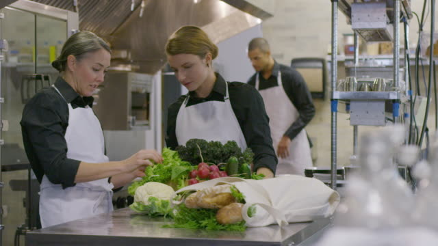 handheld shot of female chef instructing coworker while looking at vegetables with male worker in background - commercial kitchen stock videos & royalty-free footage